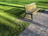 Lavička v parku vrhajúca dlhý tieň