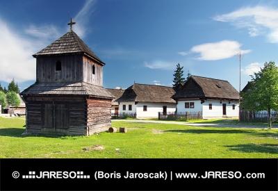 Drevená zvonica a ľudové domy v skanzene Pribylina