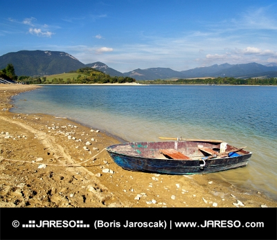Malá loďka čiastočne vytiahnutá na brehu