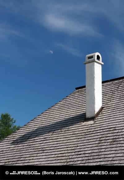 Šindľová strecha s komínom a mesiacom na oblohe