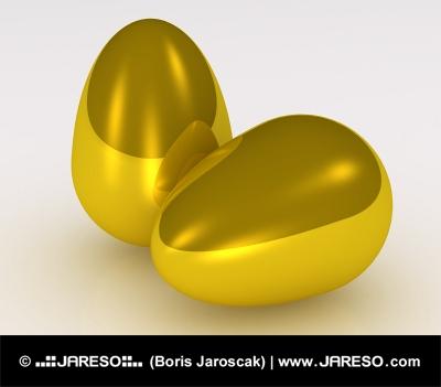 Dve zlaté zlaté vajcia na bielom pozadí